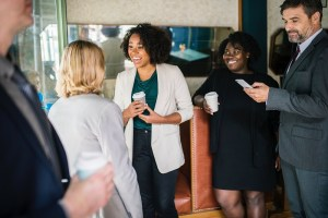 Black woman smiling and talking to peers at a networking event as others loon on admiringly