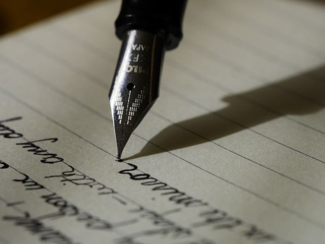 Fountain pen writing on lined paper as Marie Deveaux explains the process of writing annual reviews for your relationship in the partner review guide