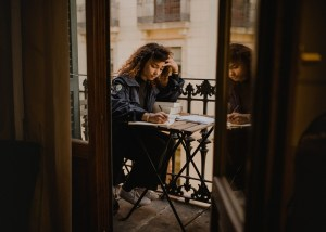 Curly haried woman sits at a table ont eh balcony with her head down in concentration as she writes in a notebook. Marie Deveaux business coach discusses writing relationship annual reviews.