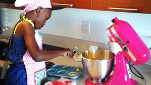 Black woman in a pink apron mixes baking batter at a kitchen aid as Marie Deveaux, business coach describes how small business owners who are still working it as a side hustle can still make baby steps towards big goals.