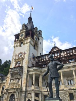 A statue in front of Peleș Castle