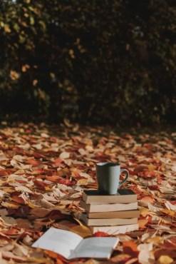 gray mug on top of piled books