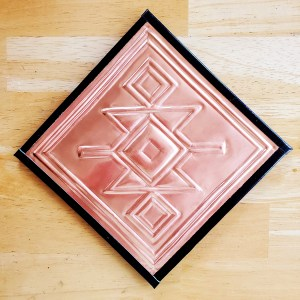A square of copper foil embossed with a Mapuche textile design from Chile
