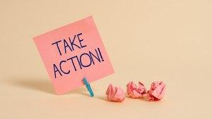 Auf einem kleinen rosa Zettel steht: Take Action!