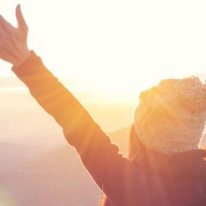Eine Frau streckt ihre Arme in die Luft und schaut zum Horizont.