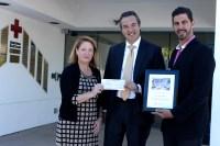 Marin Aleksov presents a check to Red Cross LA CEO Julie Thomas.
