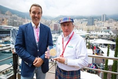 Marin Aleksov and Jackie Stewart pose with a limited-edition gold coin donated to Stewart's Race Against Dementia charity.
