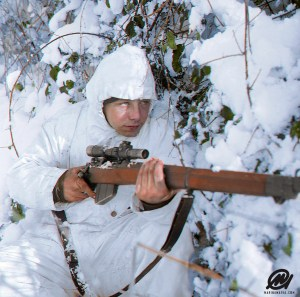 A 1st Royal Ulster Rifles, 6th Airborne Division (UK) sniper, on patrol in the Ardennes, wearing a snow camouflage suit, 14 January 1945.
