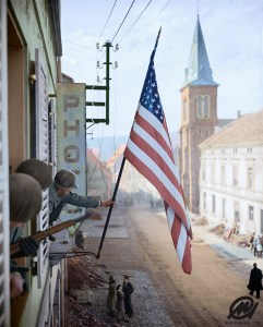 Captain Thomas H. Garahan, 'Easy' Company, 2nd Battalion, 398th Infantry Regiment, 100th Infantry Division raises the 'Stars and Stripes' flag made secretly by a local French girl.