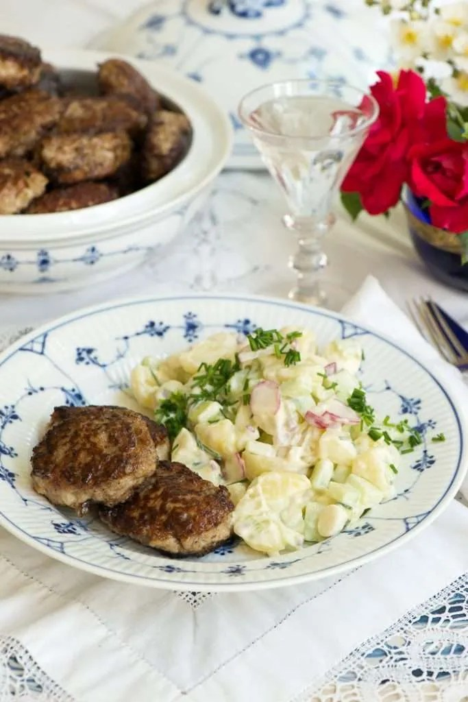 Frikadeller med kartoffelsalat serveret på musselmalet tallerken og med rød hvide blomster i baggrunden for at vise det danske
