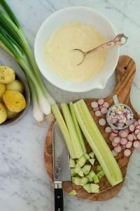 Her er ingredienserne til gammeldags kartoffelsalat.Kartofler, hjemmelavet dressing i en skål, radiser og agurk der er ved at blive skåret i tern.