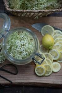 Et glas med nyplukkede hyldeblomster og citron i skiver på et skærebræt