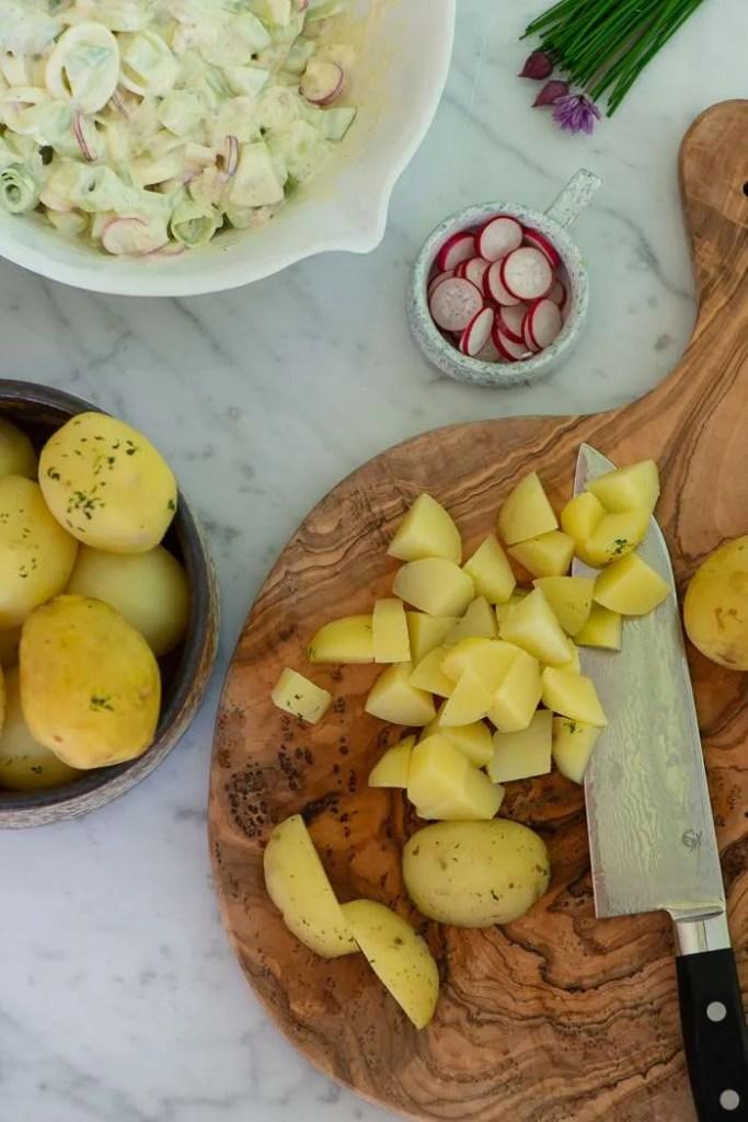 På billedet kan man se en del af ingredienserne til kold kartoffelsalt. Der er dressing med radiser og små stykker løg i en skål, der er kolde kartofler og radiser. Nogle af kartoflerne er skåret i mundrette tern.