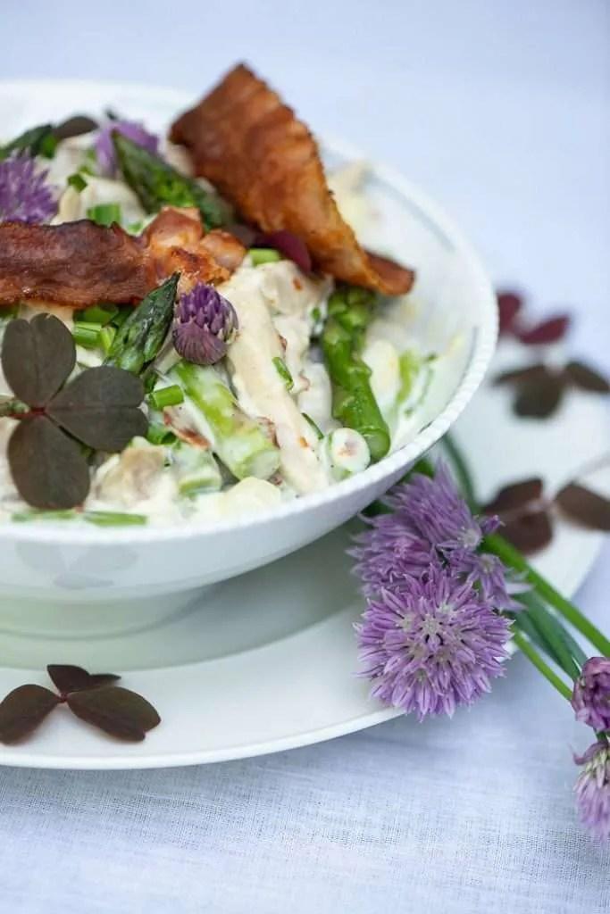 Hønsesalaten er med grønne asparges og ses her i skålen hvor der er pyntet med asparges bacon og lidt grønt