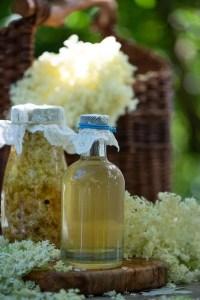 Den færdige hyldeblomsteddike og en flaske med eddike og hyldeblomster