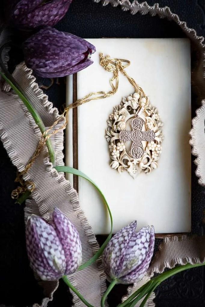 Et kors på et elfenbens omslag omgivet af ternede vibeæg. Korset skal illustrerer at Store bededag er en kristen bededag