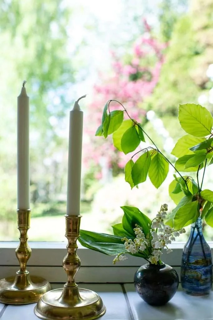 To lys, bøgegrene og blomster sat frem i vinduet for at illustrerer Danmarks 4 maj tradition. Lysene skal tændes når det bliver mørkt