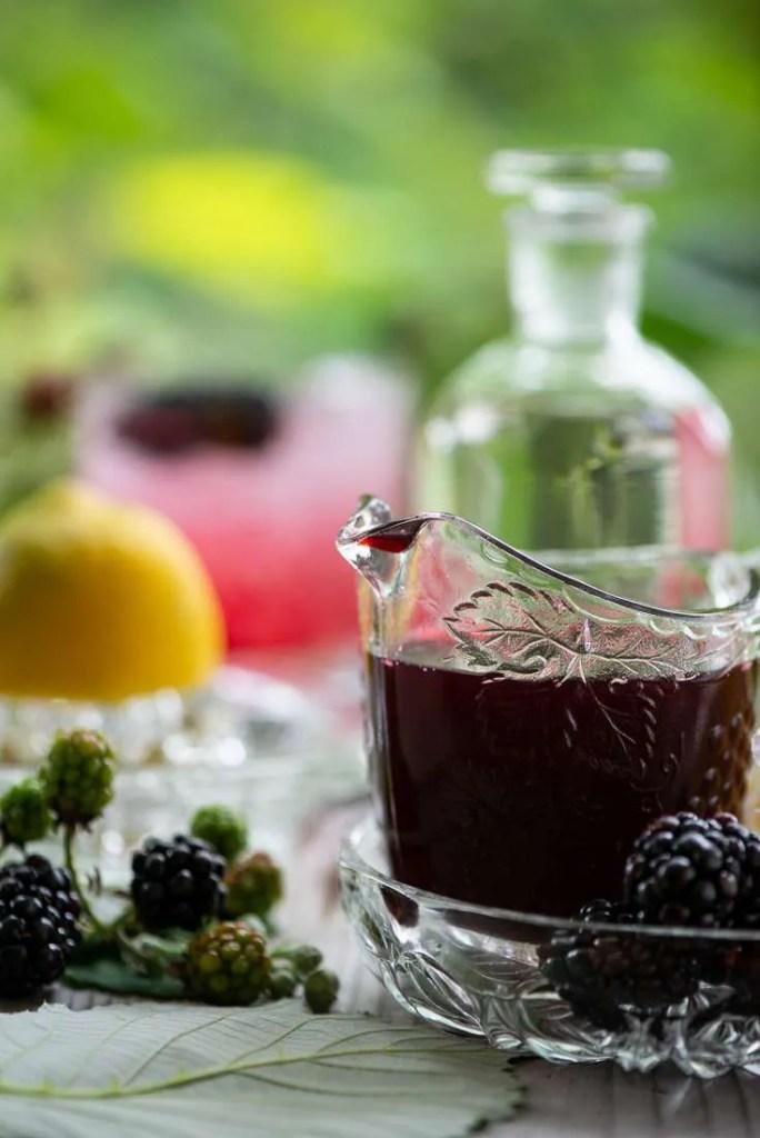 Hjemmelavet Creme de Mure med en Bramble drink i baggrunden