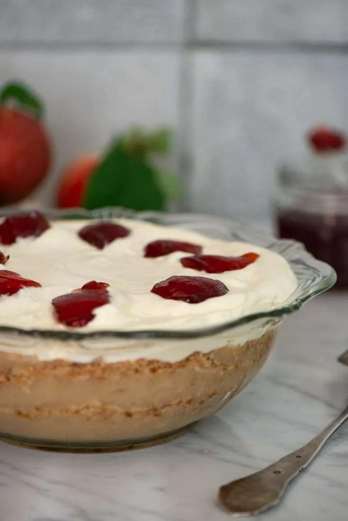 Opskrift på gammeldags æblekage. På billedet er æblekagen serveret i en glasskål så man kan se de tydelige lag. Der er flødeskum og ribsgele på toppen