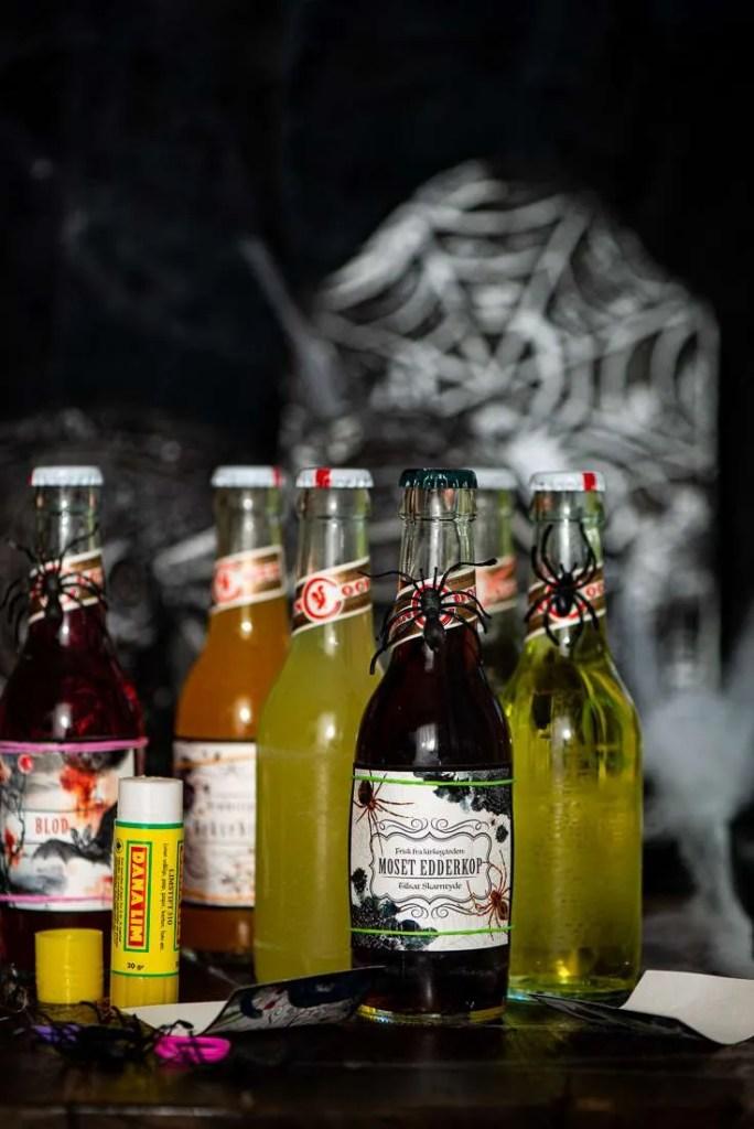 Her sættes der nye Halloween etiketter på flaskerne