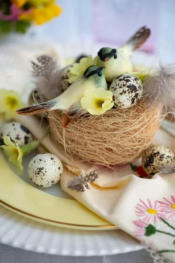 Snart påske. Bordet er dækket i forårsfarver med en fuglerede med æg og små fugle