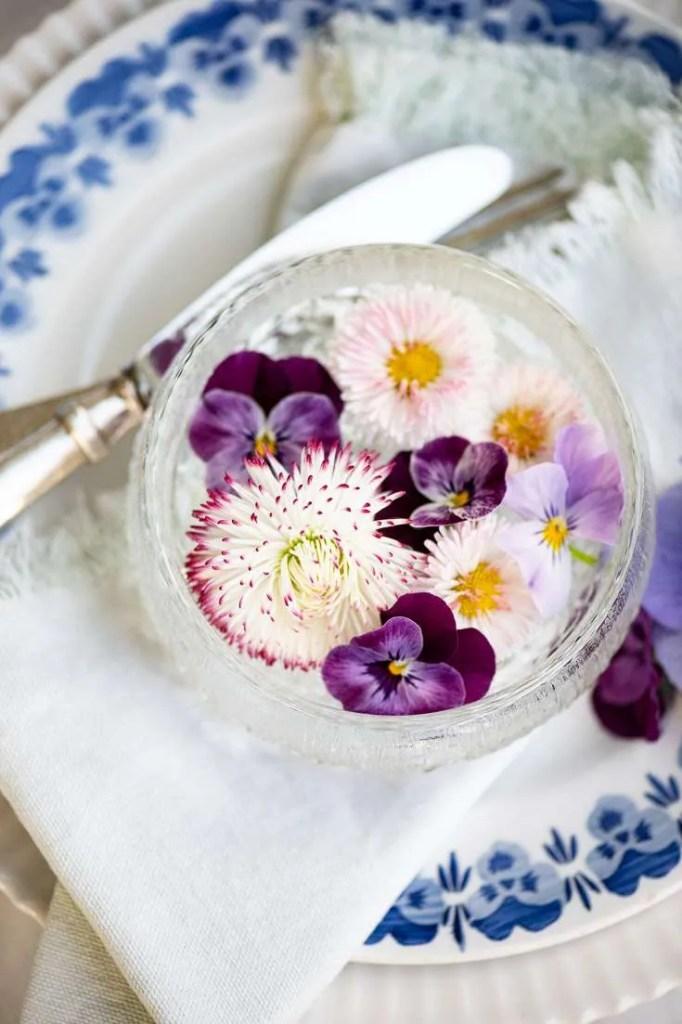 Der er dækket op med en lille skål forårsblomster og en tallerken med stedmorblomster