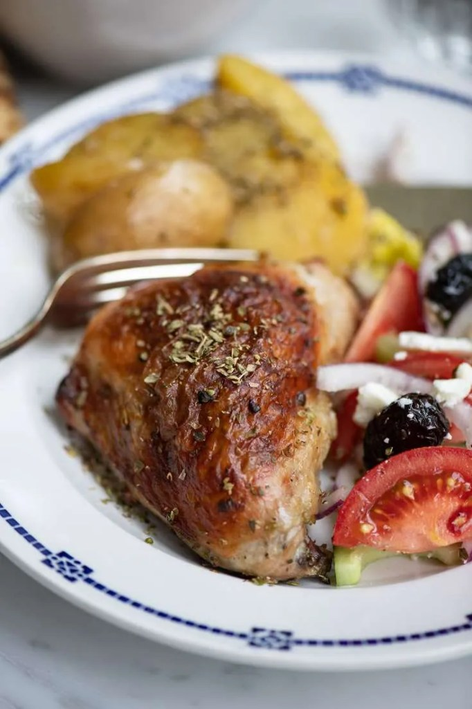 Græske kyllingelår serveret med kartofler og blandet græsk salat