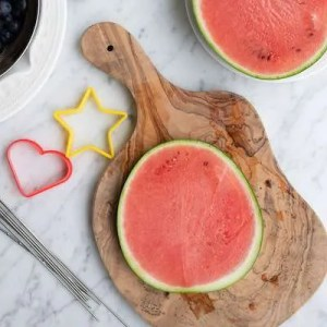 En skive vandmelon. Ved siden af udstiksforme og metal spyd