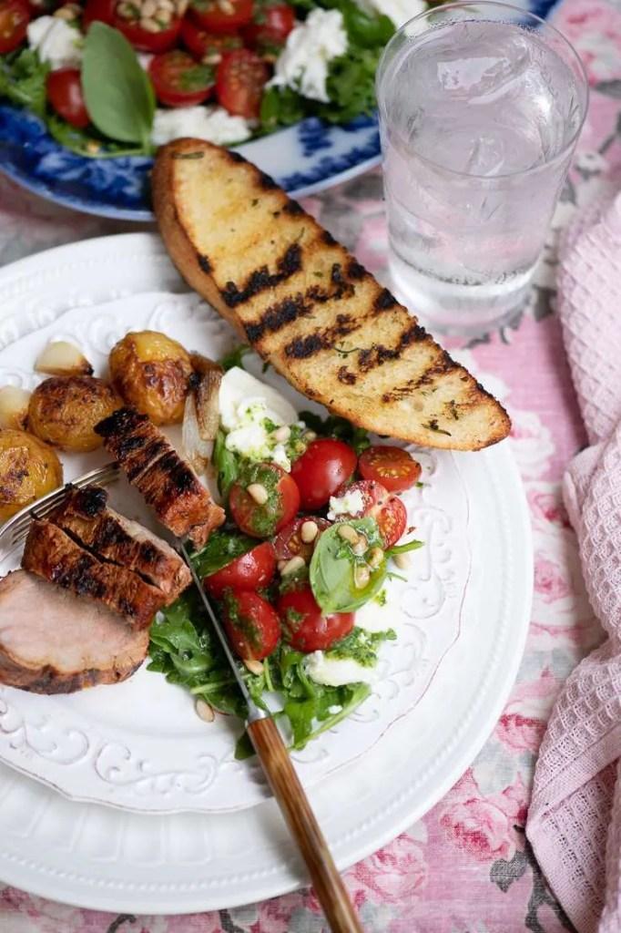 Her er tomatsalaten serveret med grillet svinemørbrad og grillede brødskiver