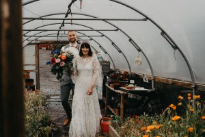 Bride and groom walking in a greenhouse and smiling