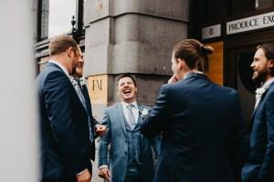 Groom laughs with his groomsmen