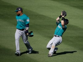 Seattle Mariners' Dan Robertson, right, calls off Robinson Cano to make a catch during the fifth inning of a spring training baseball game against the Colorado Rockies, Thursday, March 24, 2016, in Scottsdale, Ariz. (AP Photo/Darron Cummings)