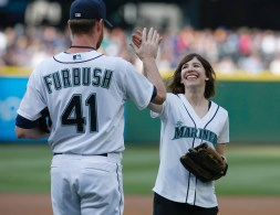 SEATTLE, WA - MAY 09: Portlandia star Carrie Brownstein is greeted by relief pitcher Charlie Furbush #41 after throwing out the ceremonial first pitch prior to the game between the Seattle Mariners and the Oakland Athletics at Safeco Field on May 9, 2015 in Seattle, Washington. (Photo by Otto Greule Jr/Getty Images)