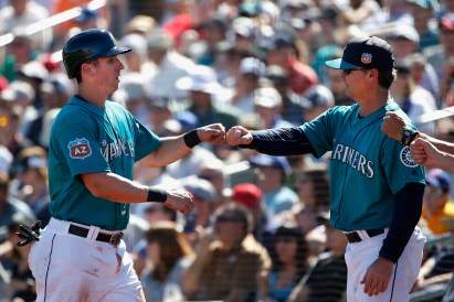 PEORIA, AZ - MARCH 10: Ed Lucas #5 of the Seattle Mariners high fives manager Scott Servais after scoring a second inning run against the Chicago Cubs during the spring training game at Peoria Stadium on March 10, 2016 in Peoria, Arizona. (Photo by Christian Petersen/Getty Images)
