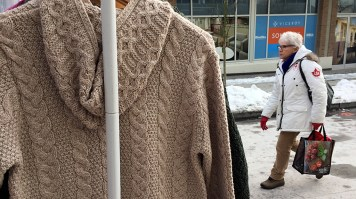 A rack of hand-knit sweaters is an enticement to shoppers trying to stay warm at Saturday's chilly Royal City Winter Farmer's Market.