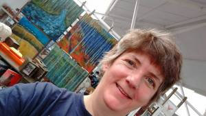 Artist Marion Boddy-Evans with her paintings in Skyeworks Gallery