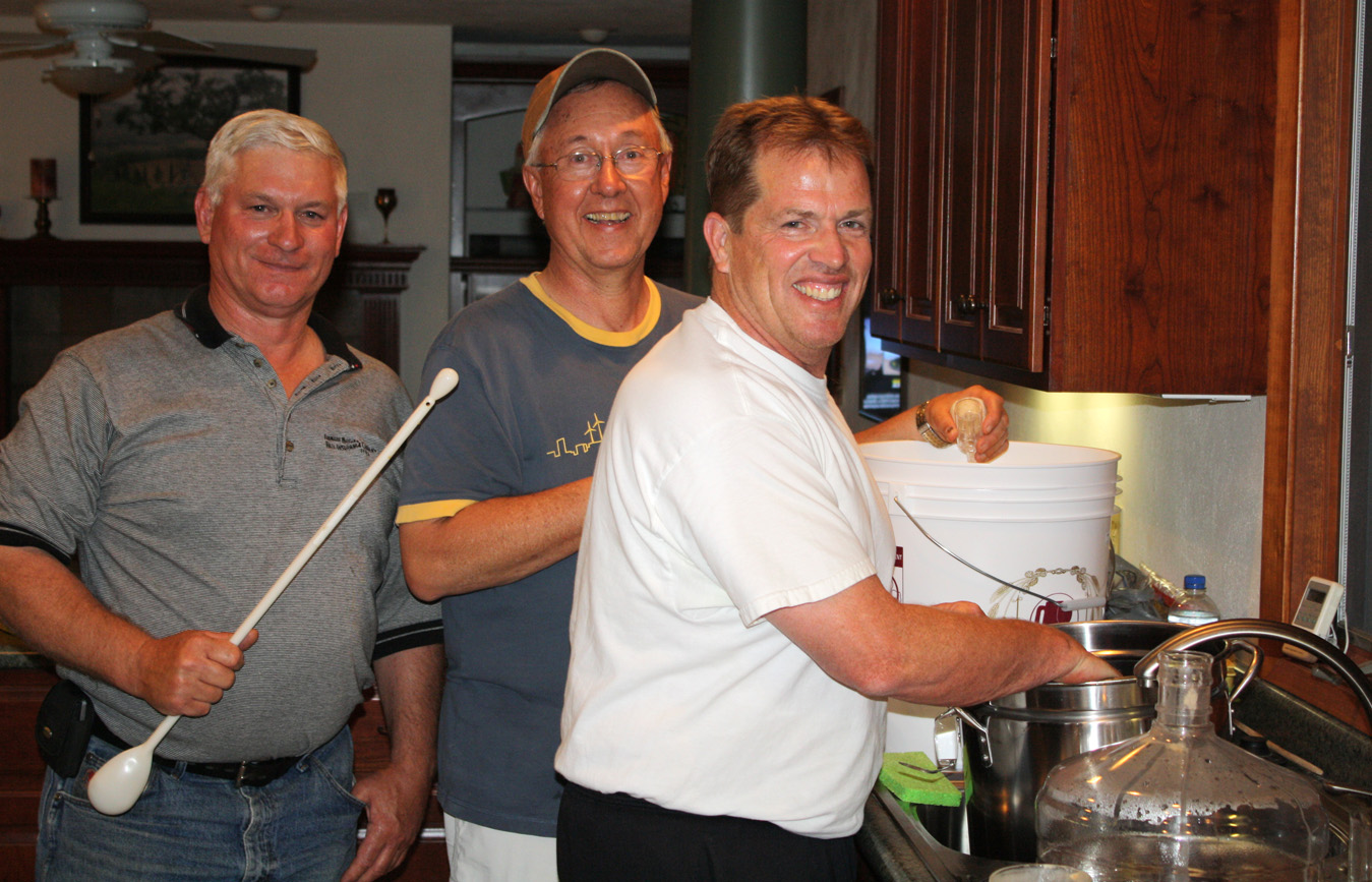 May 31, 2009.  L to R:  David Weiser, Jim Eaton and Bill Shimon transferring Bear Spit from the turkey fryer to the cargoy for fermentation.  Click photo to enlarge.