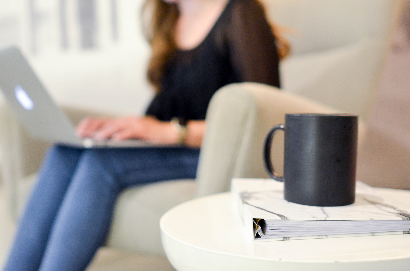 woman typing on computer with coffee, overcoming writer's block