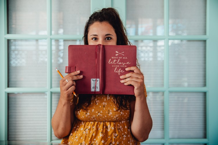 happy woman with journal hoping to avoid burnout