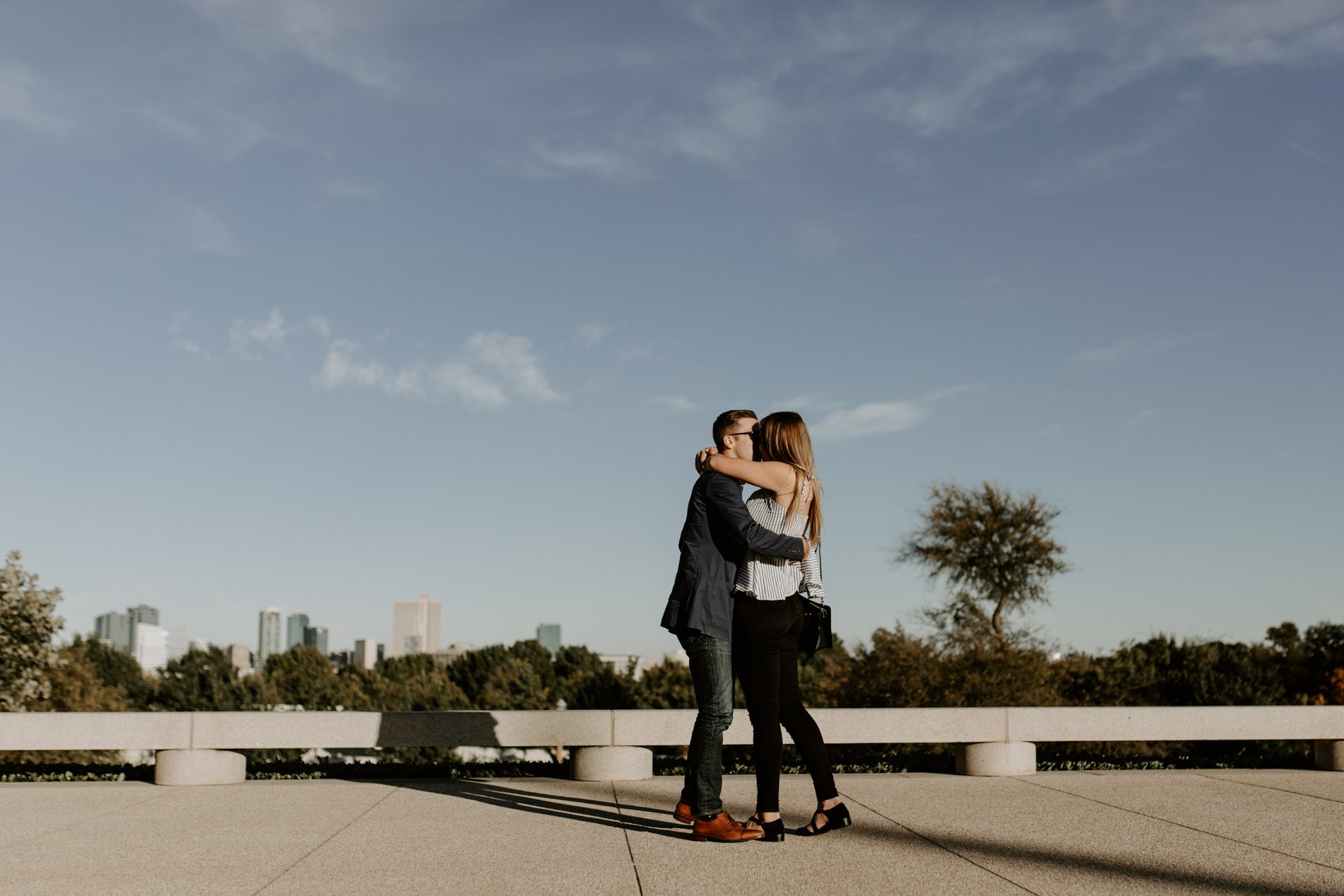 girl and boy kissing with skyline in the background