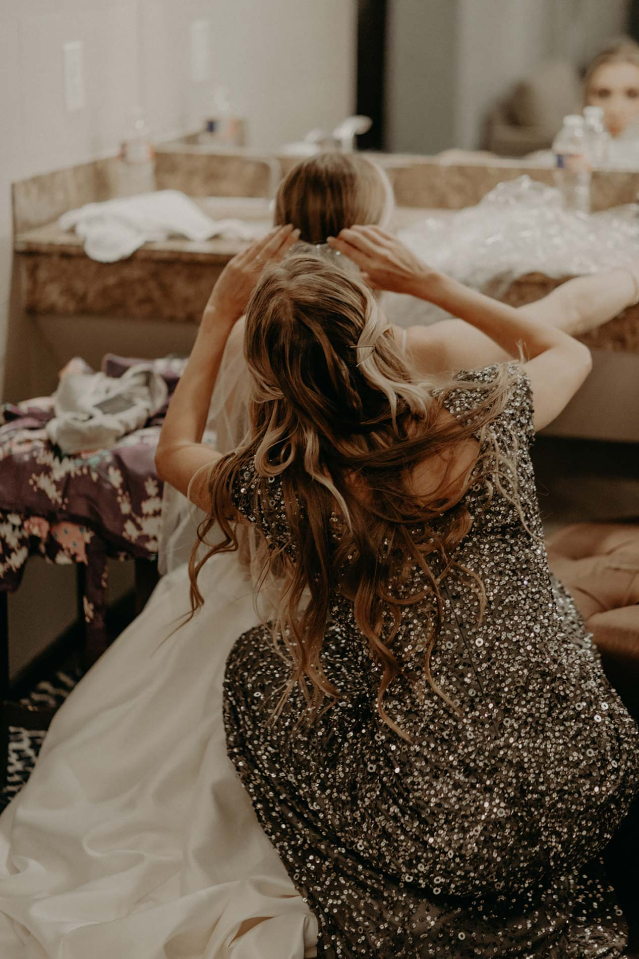 bridesmaid doing brides hair before wedding ceremony