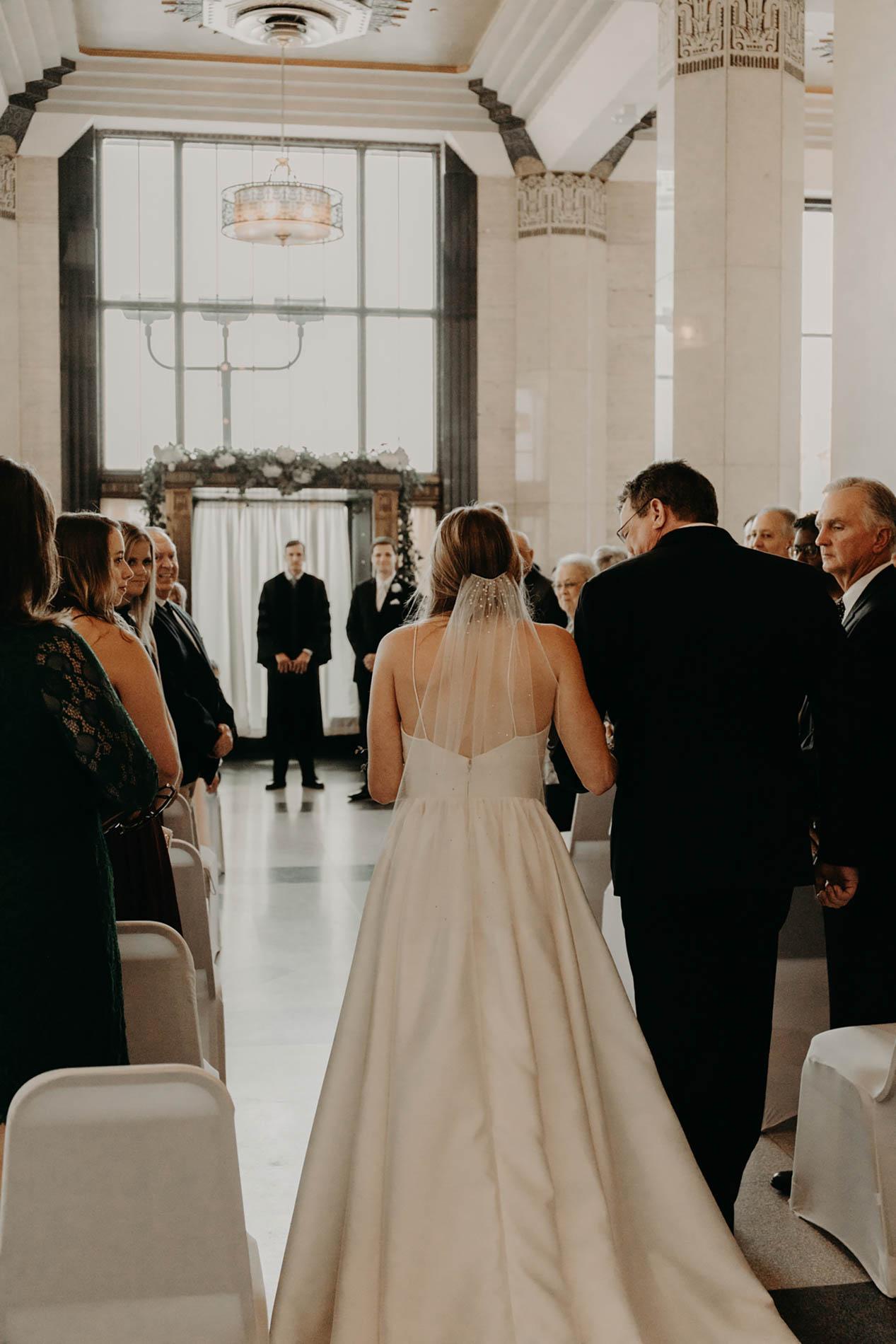 bride walking down aisle towards groom on wedding day