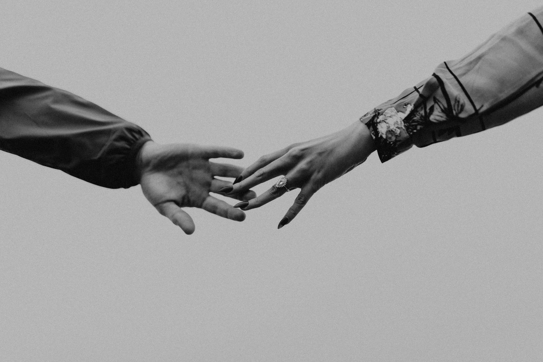 black and white engaged couple touching hands
