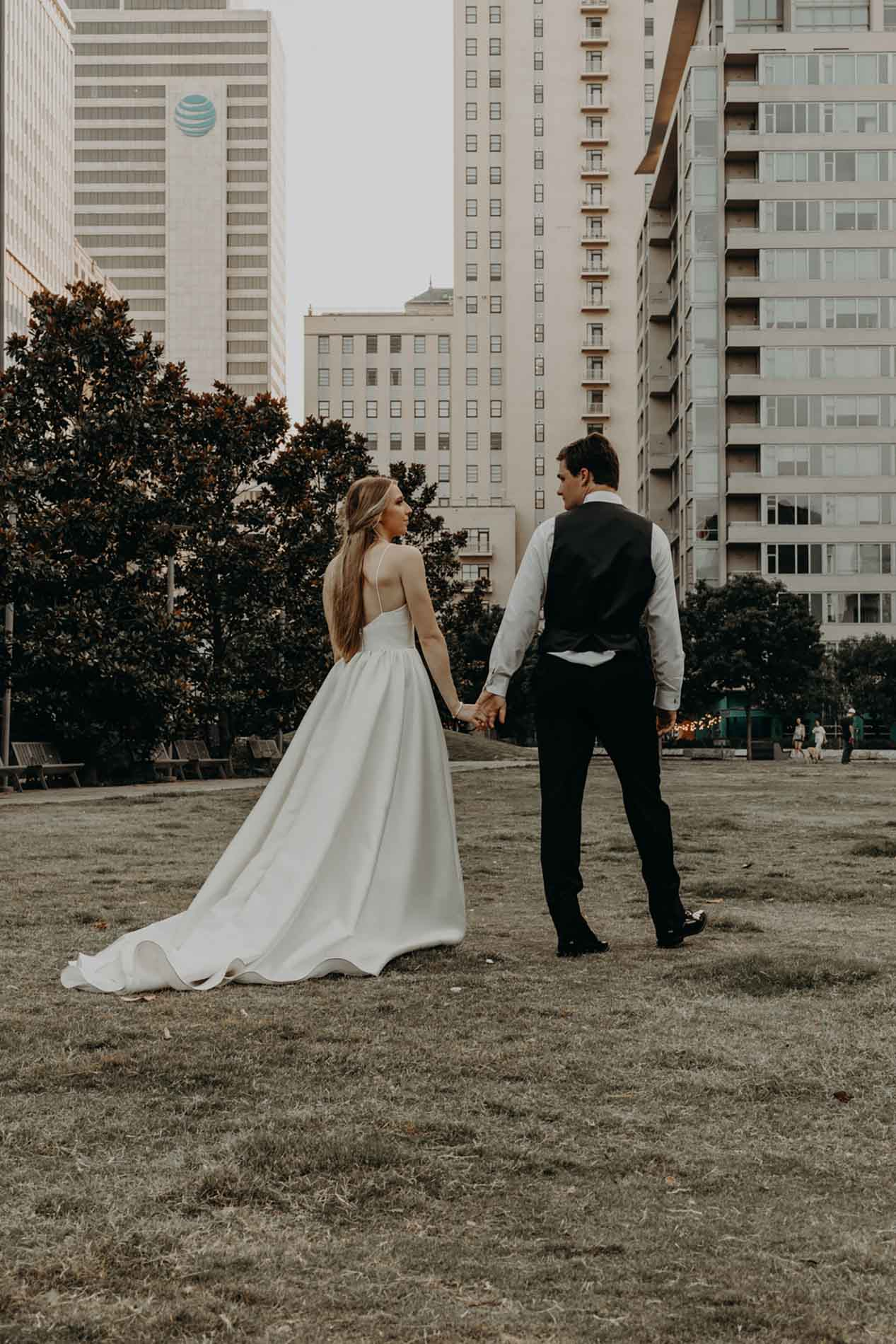 married couple walking downtown in wedding dress