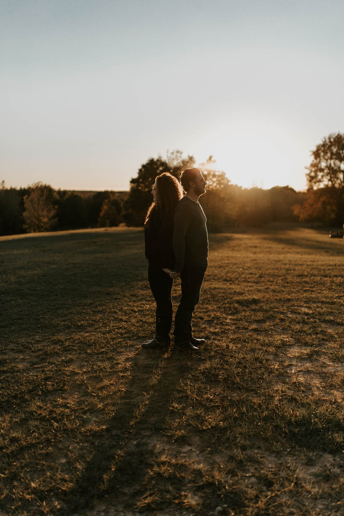 couple standing back to back at sunset