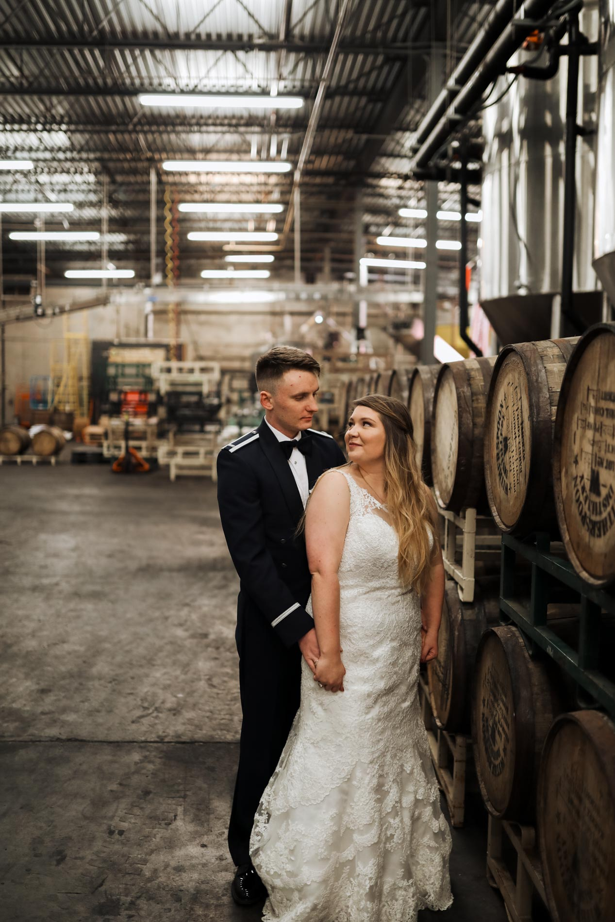 bride and groom being romantic in brewery
