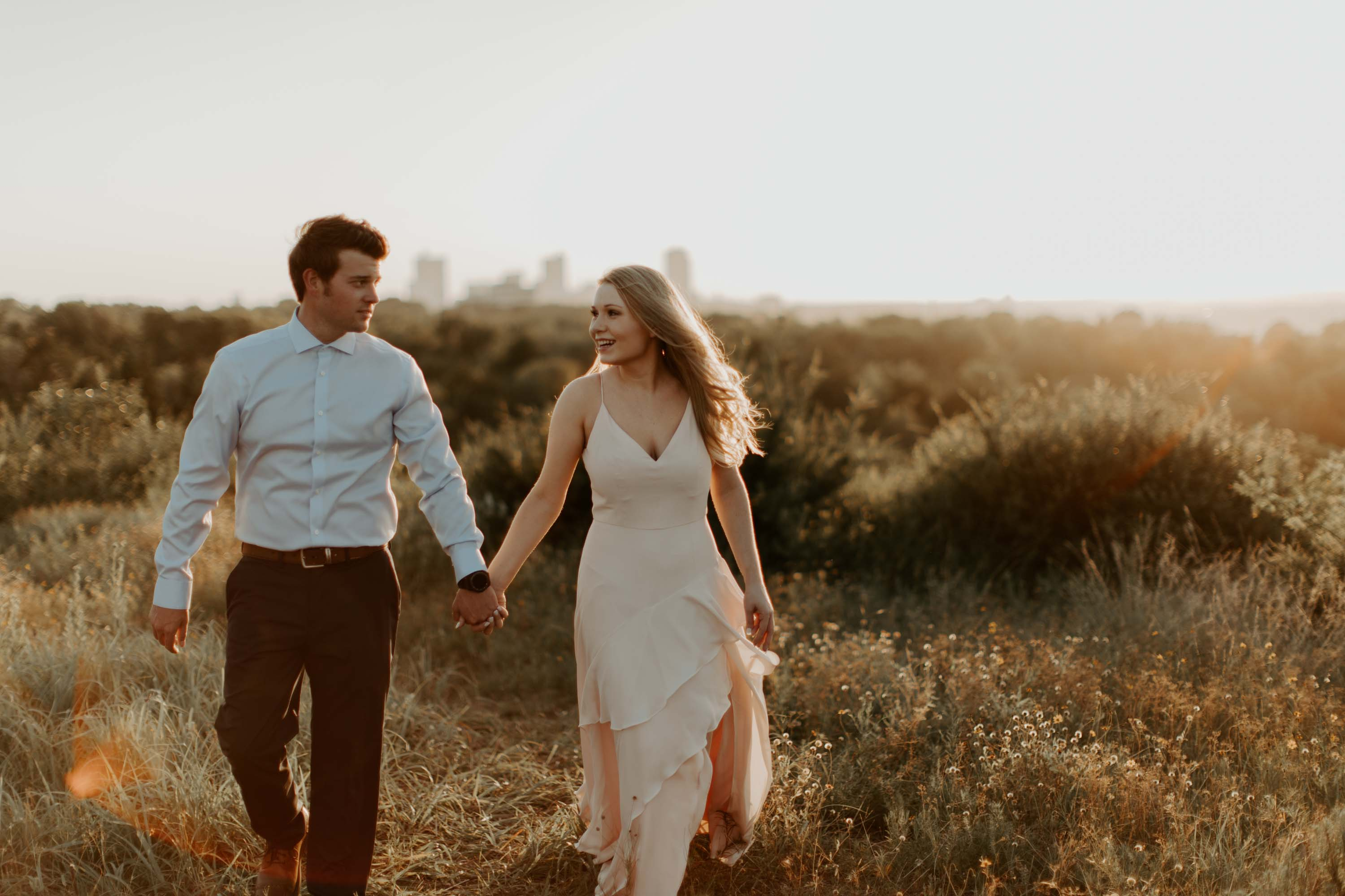 couple holding hands and walking in a field during golden hour