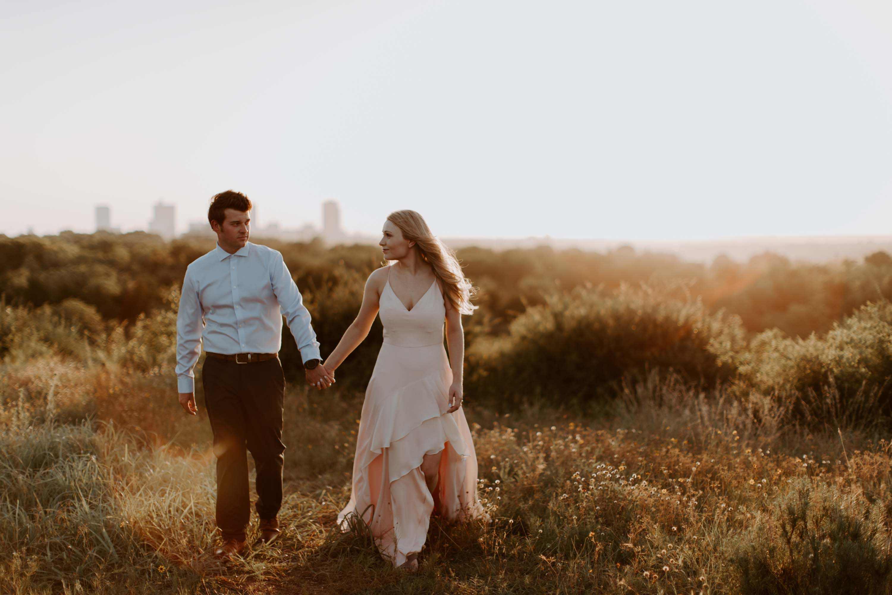 couple walking in a field at sunset