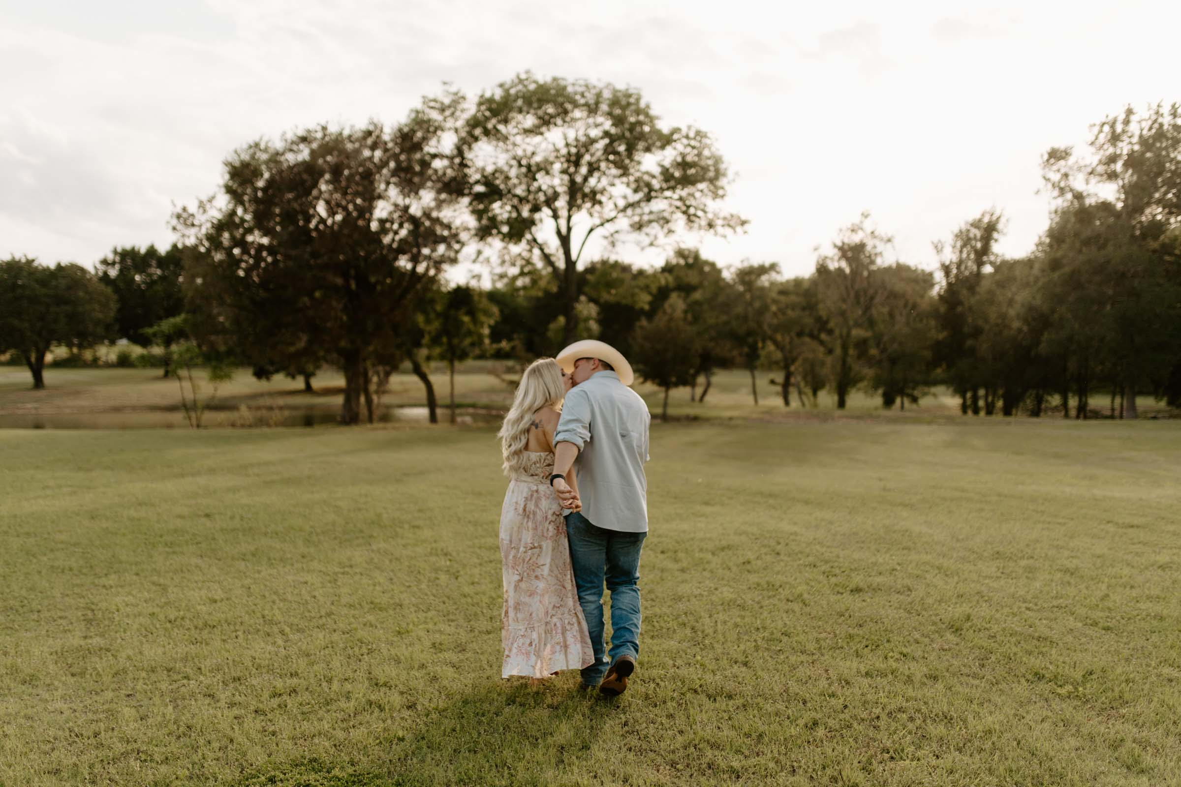 Romantic engaged couple kissing and walking in texas