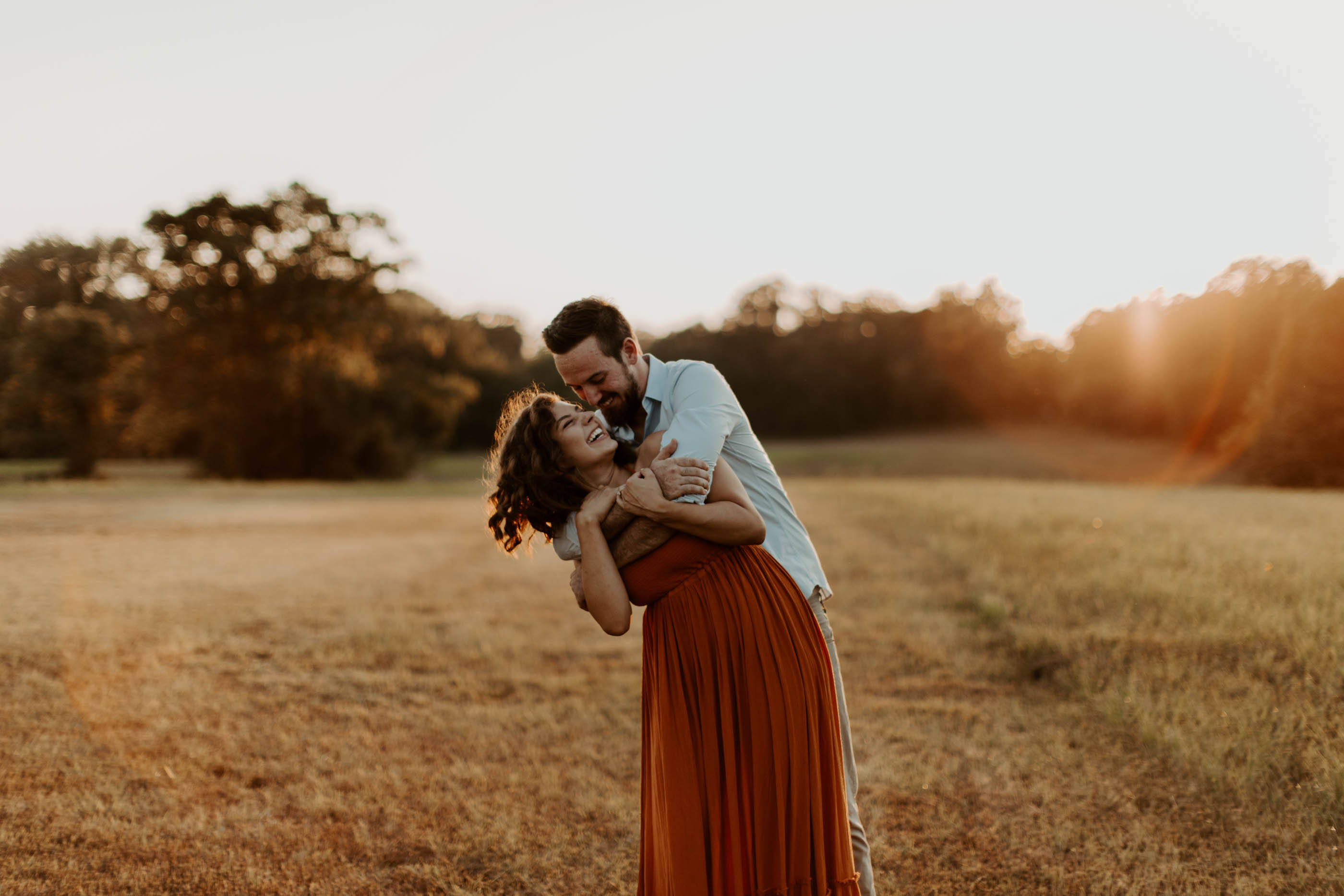 engaged couple in East Texas cuddling at golden hour